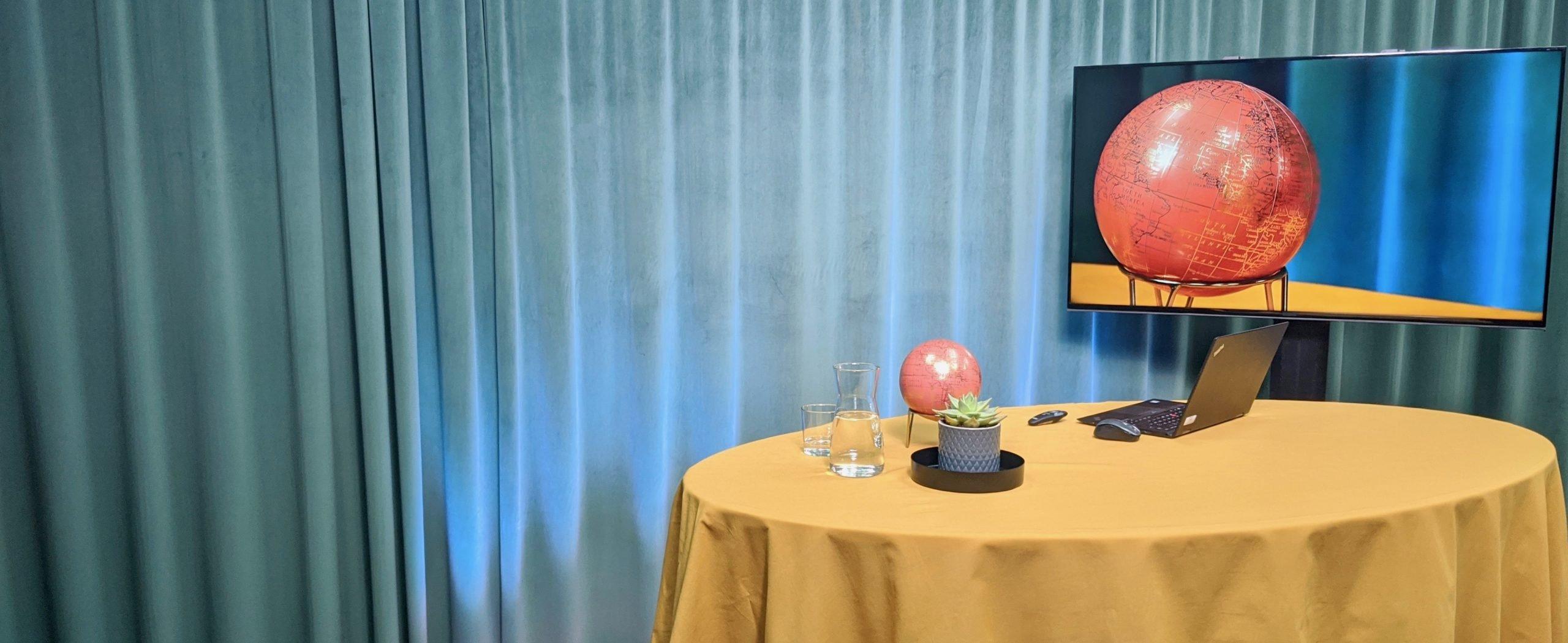 I studion står ett bord med en dator, en växt och några vattenglas. Bakom bordet står en TV som visar en jordglob.