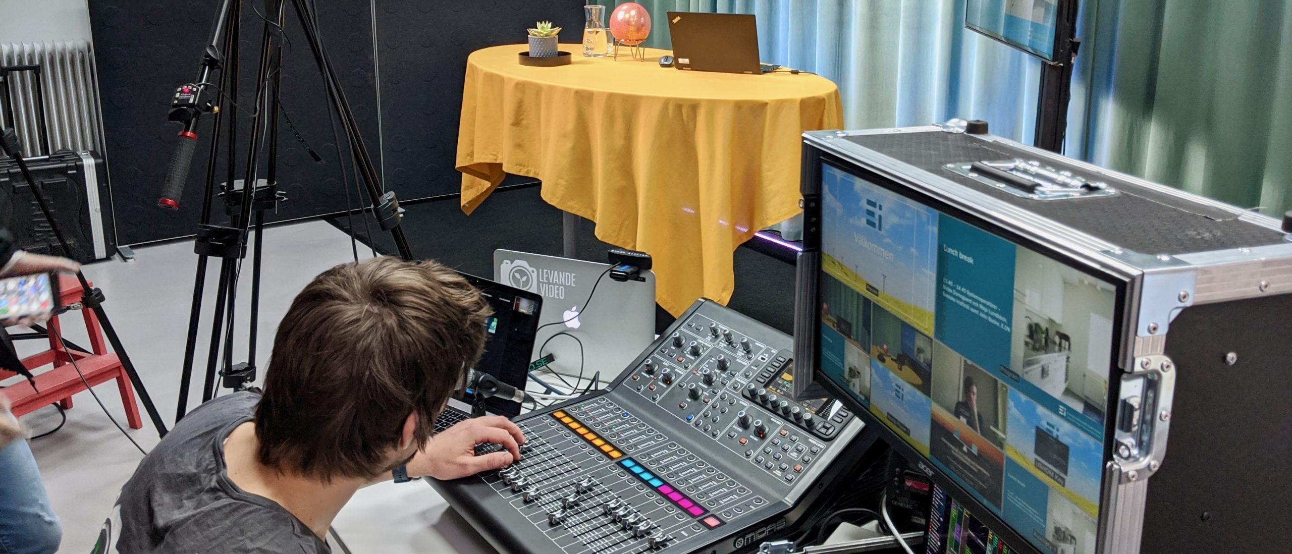Nils sitter längst bak i studion, med ljud- och bildmixer framför honom. I bakgrunden syns scenen.